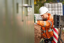 Man wearing hi vis jacket setting a container building in place