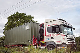 Side view of a container building unit on a lorry