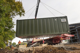 Container home unit being moved by a crane
