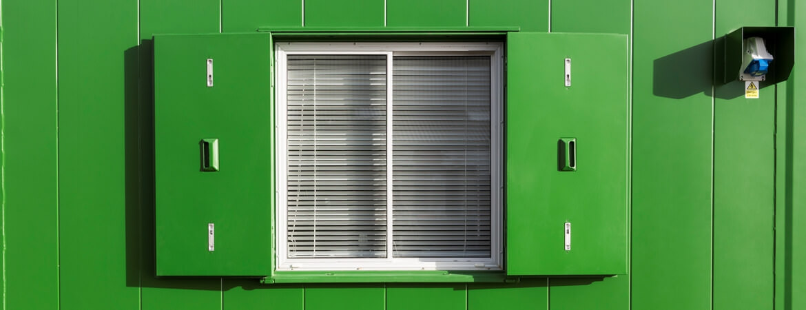 Exterior view of window with shutter of a green container home