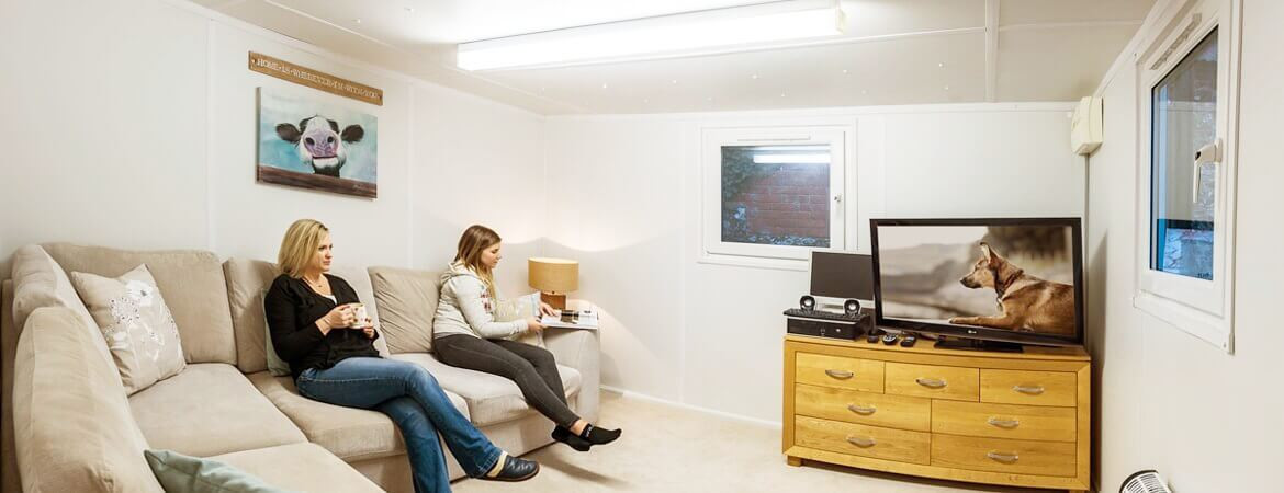 Two women watching television in container home lounge